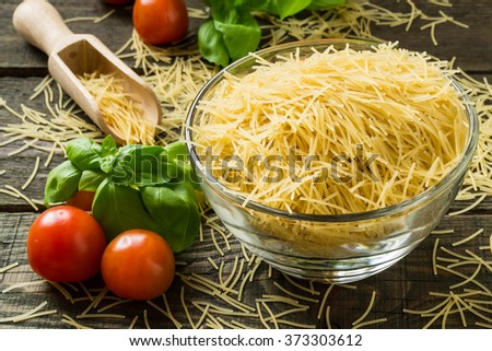 Dried pasta vermicelli, cherry tomatoes, basil, oil, prepared for cooking. Selective focus - stock photo