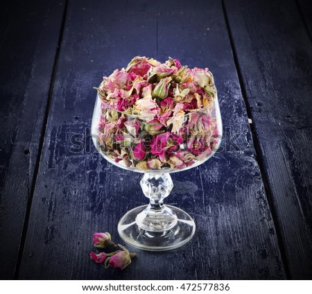 Dried pink roses heads in glass and petals on blue wooden table.