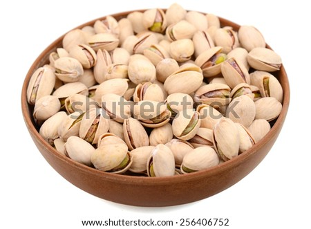 dried pistachio nuts in bowl on white background - stock photo