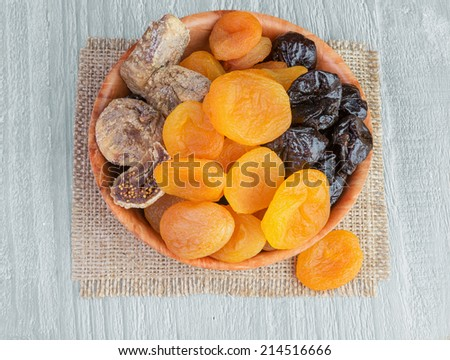 Dried pitted fruits on a wooden background  - stock photo