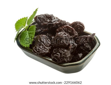 Dried plums with melissa leaves isolated on white
