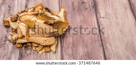Dried porcini mushroom over wooden background