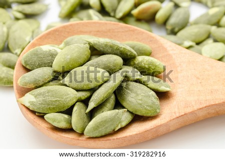 Dried Pumpkin Seeds in wooden spoon on white background. - stock photo