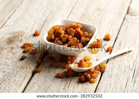Dried raisins on a grey wooden table - stock photo