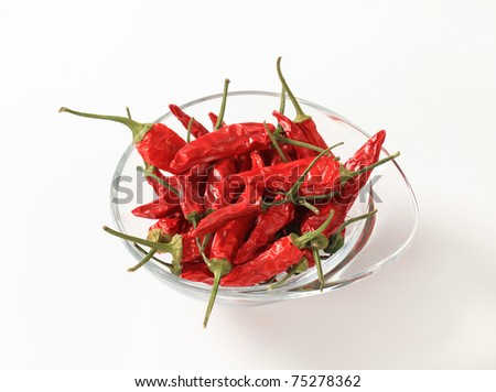 Dried red chili peppers in a glass bowl