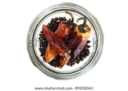 Dried red chilis pepper in a glass jar on a white background - stock photo