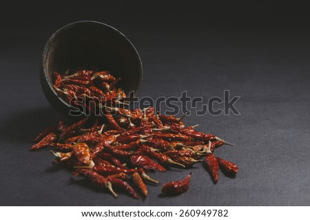 Dried red chillies spilled from a old wooden bowl on a dark background. - stock photo