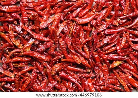 Dried red hot chilli peppers on old wooden table background - stock photo