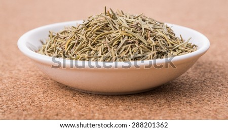 Dried rosemary herb leaves in white bowl over cork board background