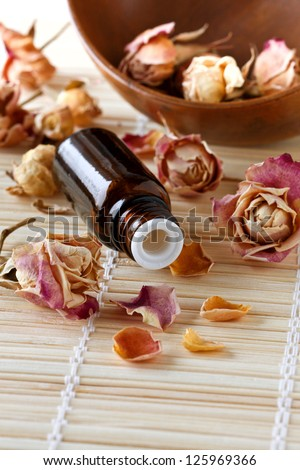 dried roses, a bottle of essential oil on a bamboo napkin - stock photo