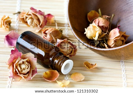 dried roses, a bottle of essential oil on a bamboo napkin,spa - stock photo