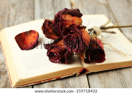 Dried roses on grey wooden background - stock photo
