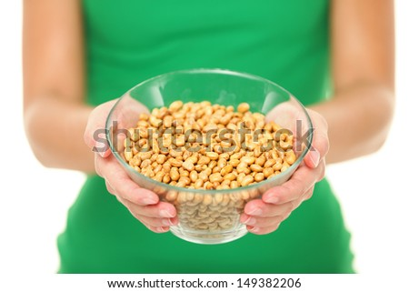Dried salty soybeans - healthy snack. Woman showing asian snack: dry soya beans isolated on white background in studio. - stock photo