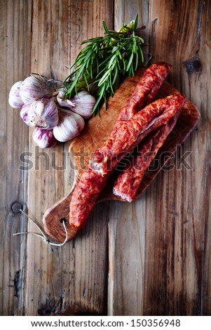 Dried sausage with garlic bulbs and fresh rosemary