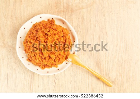 Dried shredded pork in a plate on wooden table.