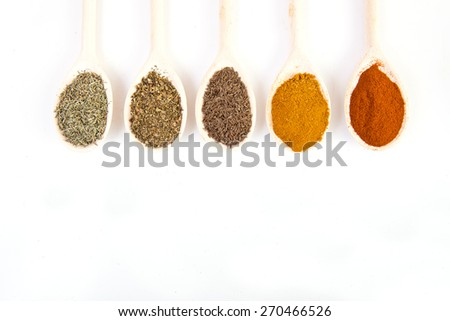 Dried spices on spoons on white background - stock photo