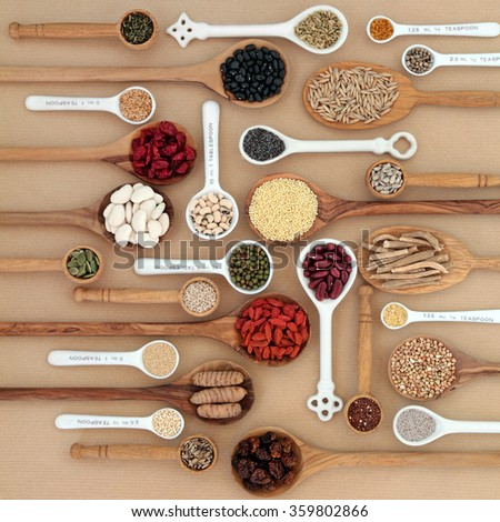 Dried superfood selection in spoons and bowls over natural paper background. Highly nutritious in antioxidants, minerals, vitamins and dietary fiber. - stock photo