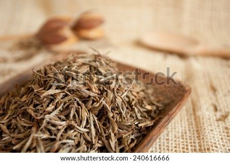 Dried tea leaves in a wooden cup, country style