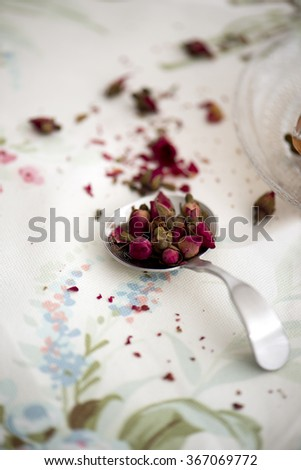 dried tea roses in a spoon - stock photo