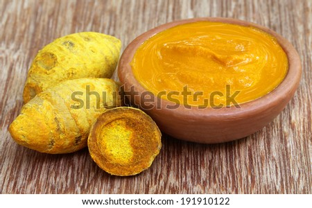 Dried turmeric with paste on wooden surface - stock photo