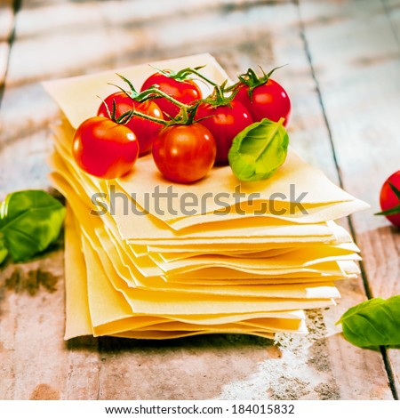 Dried uncooked lasagne pasta sheets with fresh ingredients including cherry tomatoes and basil leaves, close up on old wooden boards - stock photo