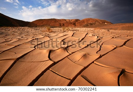 Dried up and cracked river bed with hills in the distance - stock photo