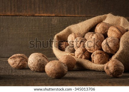 Dried walnuts in a sack on a wooden rustic background