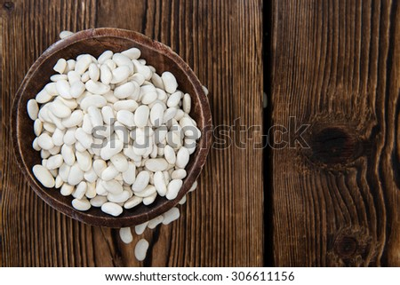 Dried White Beans (close-up shot) on wooden background - stock photo