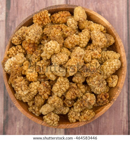 Dried white mulberries in wooden bowl over wooden background