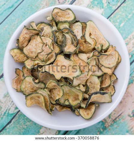 Dried zucchini or courgette in white bowl over wooden background - stock photo