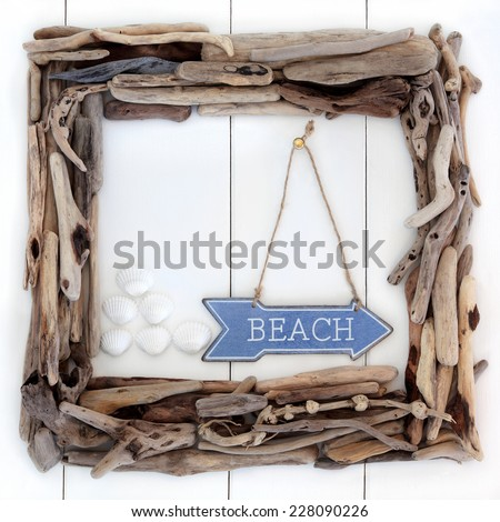 driftwood frame and beach sign with cockle shells over wooden white background