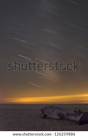Driftwood log on beach with star trails over water - stock photo