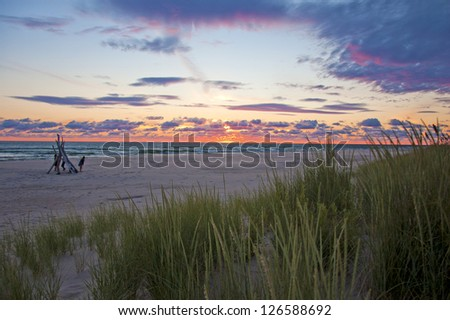 Driftwood tipi on beach with dramatic sun and sky - stock photo