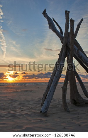 Driftwood tipi on beach with dramatic sunlight - stock photo