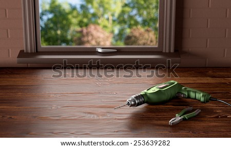 drill and pliers on a background of vintage wooden table and brick wall - stock photo
