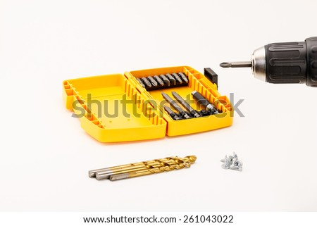 Drill chuck, drill bits, screw bits and screws on white background. - stock photo