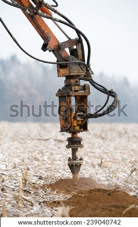 Drilling rig boring holes in ground during construction geodesy works - stock photo