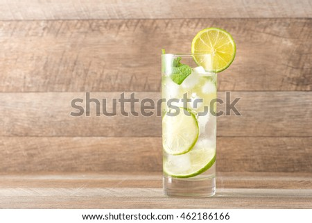 Drink for hot summer days. Fresh lime and lemon lemonade with mint in a glass on a wooden desk