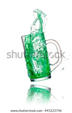 Drink green splash out of glass on a white background.