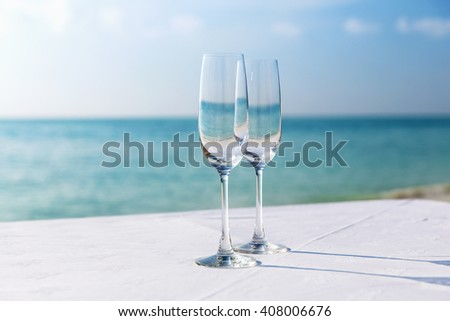 drink, holidays, summer vacation  and celebration concept - close up of two champagne glasses on table over sea  on beach  - stock photo