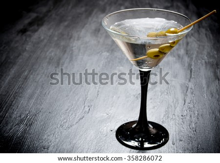 Drink martini. Martini with olives on a black table. Free space for text. - stock photo