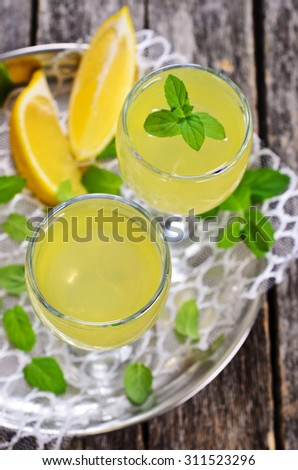Drink of lemon in a small glass on a wooden surface