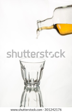 Drink responsibly; Drink aware; Don't drink and drive. Whiskey freezes in the air after coming out of bottle. Isolated, white background. Art in food and drink. - stock photo