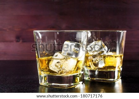 drink series, two glasses of whiskey with ice on old wood table,  pub atmosphere - stock photo