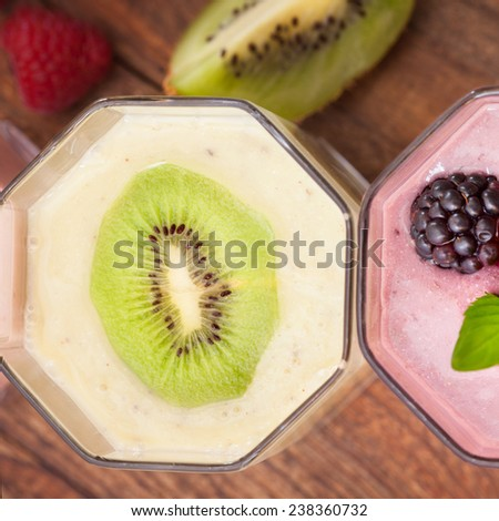Drink smoothies four summer strawberry, blackberry, kiwi, raspberry on wooden table. - stock photo