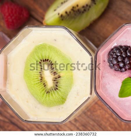 Drink smoothies four summer strawberry, blackberry, kiwi, raspberry on wooden table. - stock photo