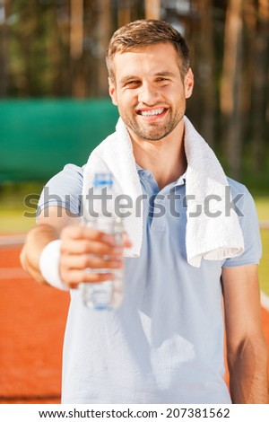 Drink some water! Happy young man in polo shirt and towel on shoulders stretching out bottle with water while standing on tennis court  - stock photo