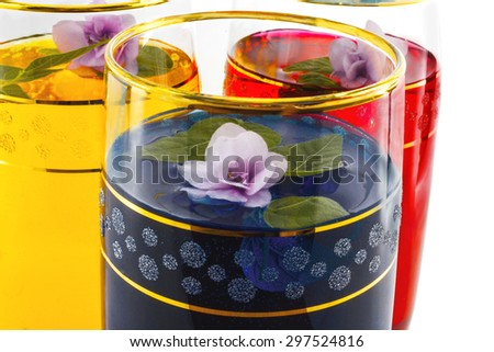 drink three colors of flowers, close-up, blue, white background - stock photo