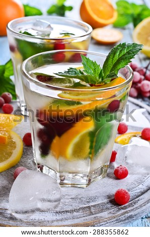 Drink with lemon, orange, berries and mint in a glass with ice - stock photo