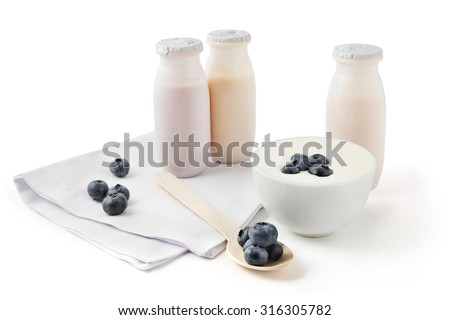 Drink yogurts in plastic bottles and in a bowl with blueberries